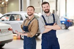 Two Workers in Car Service. Waist up portrait of two handsome bearded workers smiling at camera while posing  in production workshop of modern car factory, copy Stock Images