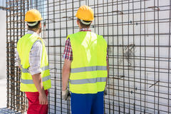 Two workers checking the durability of the steel structure of a. Two blue-collar workers wearing safety equipment, while checking the durability of the steel royalty free stock photos