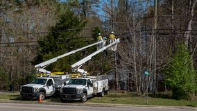Two workers in a cherry picker bucket. Working on electrical wires stock photography