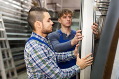 Two workers choosing PVC window profile Stock Images