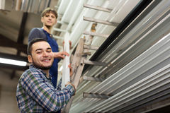 Two workers choosing PVC window profile Royalty Free Stock Images