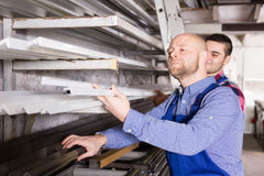 Two workers choosing PVC window profile Stock Image