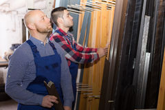 Two workers choosing PVC window profile Stock Photos