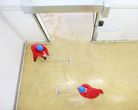 Two workers cleaning floor in industrial building. Overhead view of two workers in red uniforms and blue hardhats cleaning floor in industrial building royalty free stock photos
