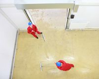 Two workers cleaning floor in industrial building. Overhead view of two workers in red uniforms and blue hardhats cleaning floor in industrial building stock photography