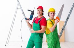 Two workers contractors working indoors. The two workers contractors working indoors royalty free stock image