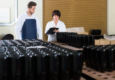 Two workers controlling number of wine bottles at sparkling wine Royalty Free Stock Photo