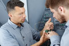 Two workers dealing with electricity indoors royalty free stock photo