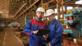 Two workers discuss a construction project. Engineer-constructor and worker discuss the construction project against the background of an industrial plant stock video