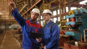 Two workers discuss a construction project. Two industrial workers in construction helmets discuss the project stock video footage
