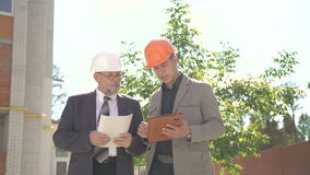 Two workers discussing scheme of building near builds. 4K stock video