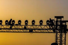 Workers on concert structure in the sunset backlight. Two workers are dismounting the irony structure that holds the lights, during the sunset. Backlight image Royalty Free Stock Photography