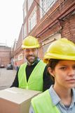 Two workers of a forwarding company as delivery service. Two workers of a forwarding agency as a delivery service in front of a factory or a depot stock image