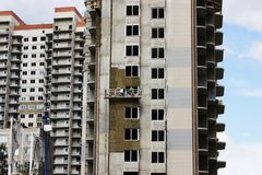 Two workers in front suspended cradle on a newly built high-rise building.  royalty free stock photo