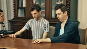 Two workers get berated by boss at office table with wood bookcase on background stock footage