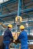 Two workers handling heavy loading lifted by crane. Two Asian workers handling heavy loading lifted by crane in the interior of a metallurgical factory stock photo