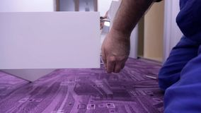 Two workers hands in checkered shirt put the white bed's frame together. Two men are assembling new furniture in freshly painted room. They use compact cordless stock video