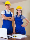 Two workers in helmets with laptop Stock Images