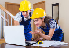Two workers in helmets with laptop Royalty Free Stock Photography