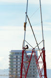 Two workers install a lot of Metal tiered tower. Stock Photography