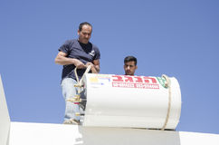 Two workers install solar boiler roof- Mitzpe Ramon, Israel Royalty Free Stock Photos