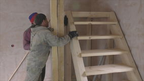 Two workers install wooden staircase stock footage