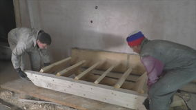 Two workers install wooden staircase stock video