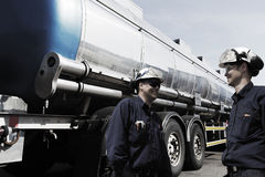 Two workers with large fuel truck in the background Royalty Free Stock Photo