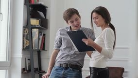 Two workers laughing and discussing work. Office workers standing near office desk and view business documents.Young man and woman discussing documents and stock footage