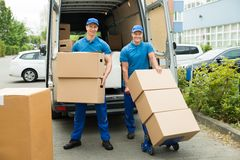 Two Workers Loading Cardboard Boxes In Truck. Two Happy Male Workers Loading Stack Of Cardboard Boxes In Truck Stock Photos