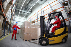 Two workers  loading pallets  with  forklift truck Royalty Free Stock Photos