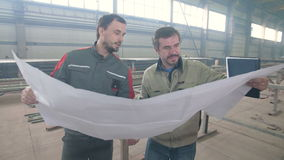 Two workers look at the drawing at the factory. Two workers look at the drawing at the factory stock video footage