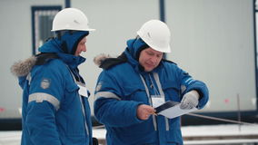 Two workers look at papers stock footage
