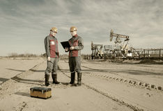 Two workers in the oilfield Royalty Free Stock Photos