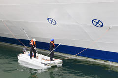Two workers paint board of cruise liner Stock Images