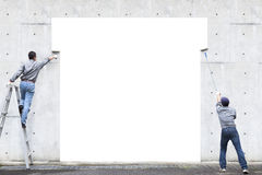Two workers are painting blank area. On the wall stock photo