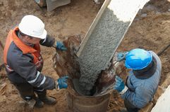 Two workers at piling. Couple workers making pile form filling with continuous concrete casting Stock Photography