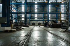 Two workers planning manufacturing process. In the interior of an industrial hall stock photo