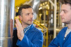 Two workers at plant checking parameters pressure Royalty Free Stock Images