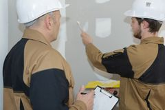 Two workers plastering wall Stock Images