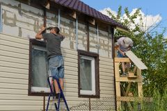 Two workers polish the apartment building with vinyl siding. August 6, 2017: two workers polish the apartment building with vinyl siding. Moskakassy. Chuvashy stock photo