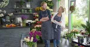 Two workers posing back to back. SIde view of young cheerful coworkers in striped aprons standing back to back with hands crossed posing in floral shop stock footage