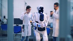 Man and woman fix a droid in a room. stock footage