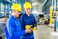 Two workers in production plant as team. Discussing, industrial scene in background Stock Image