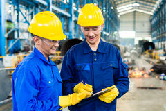 Two workers in production plant as team. Discussing, industrial scene in background Stock Photos