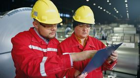 Two workers in production plant as team discussing, industrial scene in background.  stock footage