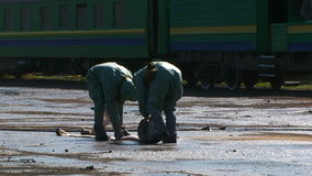 Two Workers In Protective Clothes Rolling Water. This is a shot of two workers in protective equipment rolling water hose after extinguishing fire at the railway stock footage