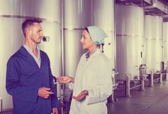 Two workers in protective uniform talking in secondary fermentat Stock Photo