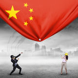 Two workers pulling Chinese flag. Image of two young businesspeople pulling a big Chinese flag, shot outdoors Stock Images