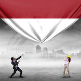 Two workers pulling Indonesian flag Stock Image